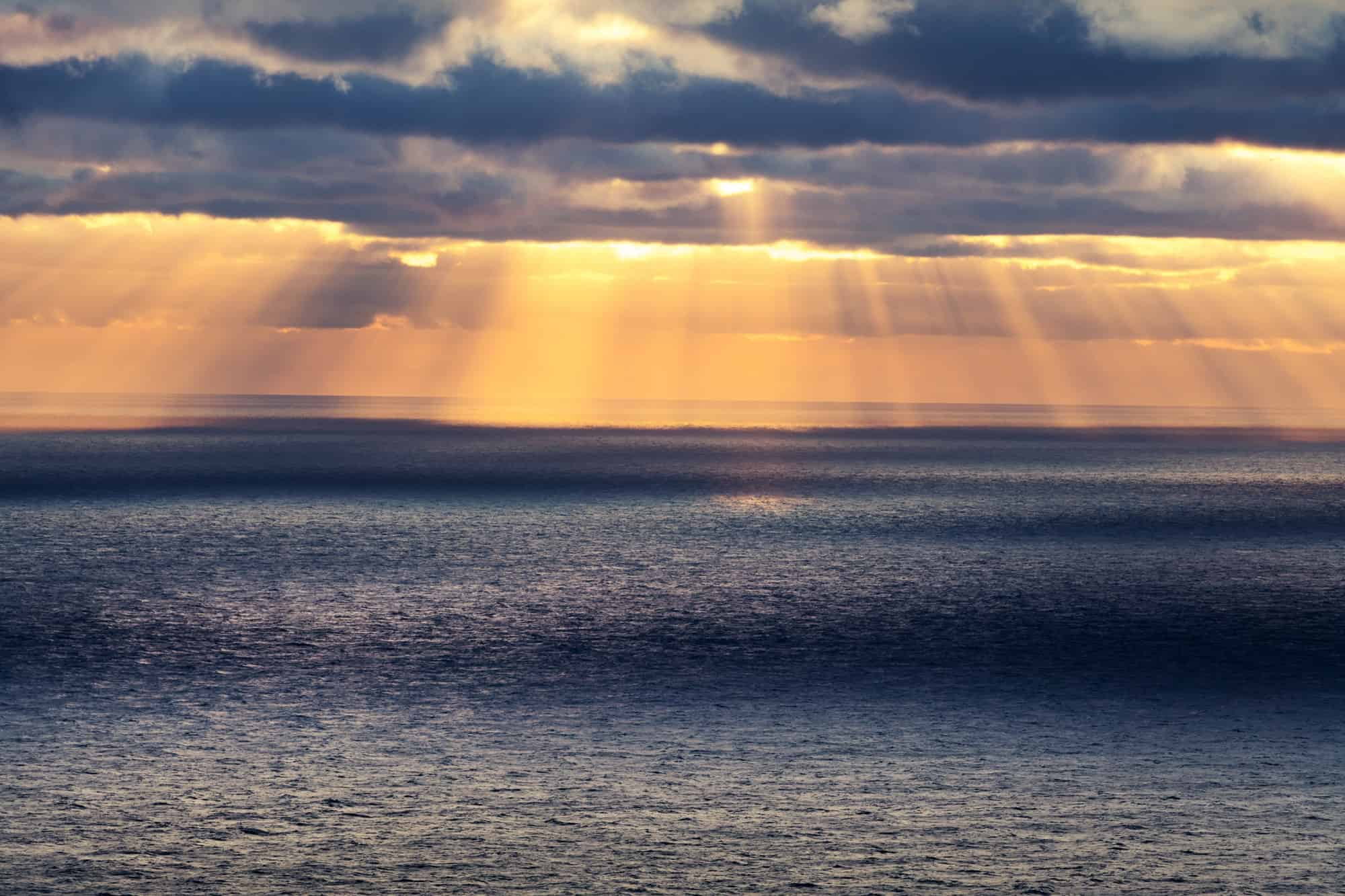Sunset in the ocean with glowing sun rays